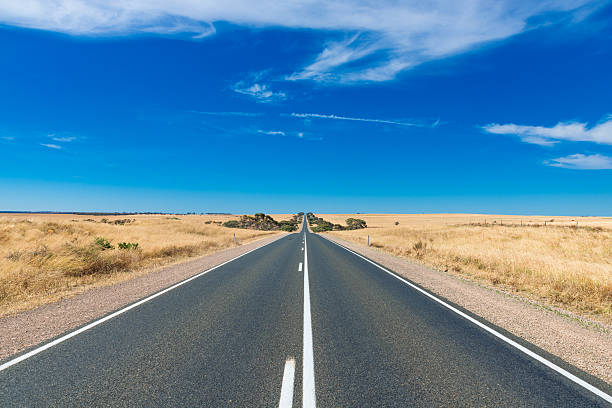 Straight line Australian highway in rural outback stock photo