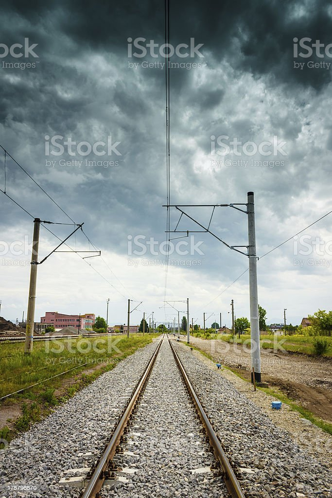 Straight railroad with dark cloudy sky royalty-free stock photo