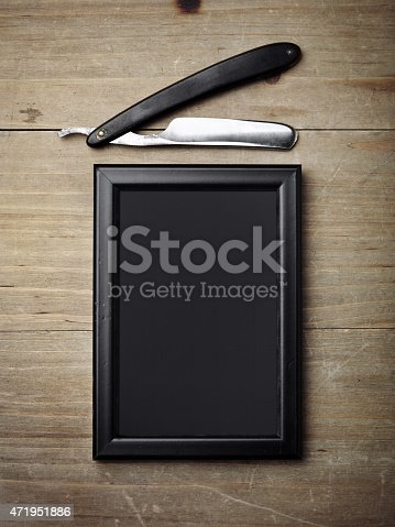 istock Straight razor and black picture frame on wood desk 471951886