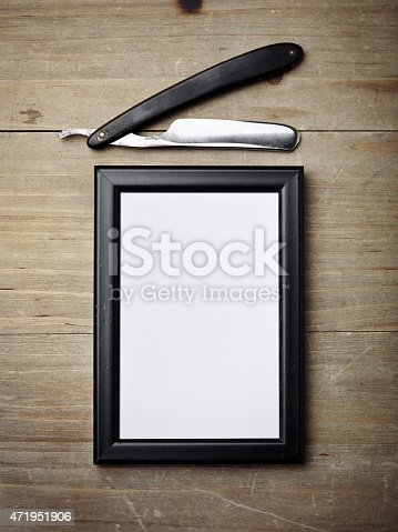istock Straight razor and picture frame on wood desk 471951906