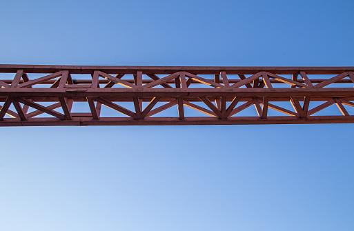 straight red steel welded girder beam on blue sky background