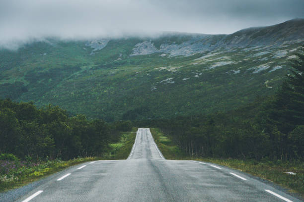 Straight road against mountainside. Straight road against mountainside in fog. middle of the road stock pictures, royalty-free photos & images