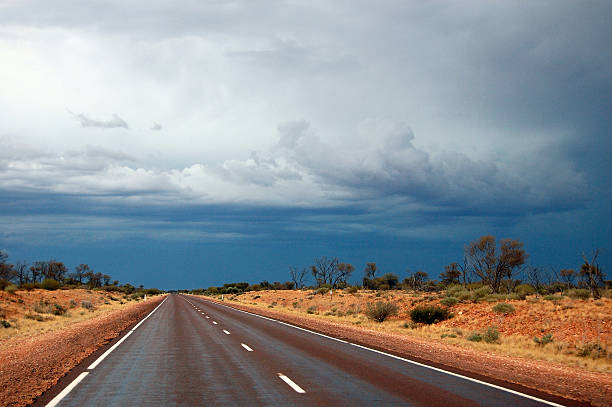 straight road at australian outback cloudy sky - darwin stock photos and pictures