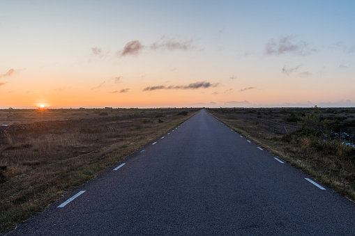 istock Straight road by sunrise in a great barren landscape 1173404648