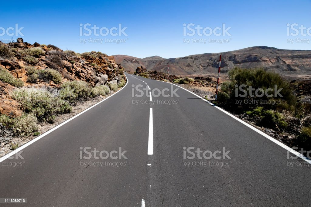 Desert road with rocks and blank signage. straight in perspective of...