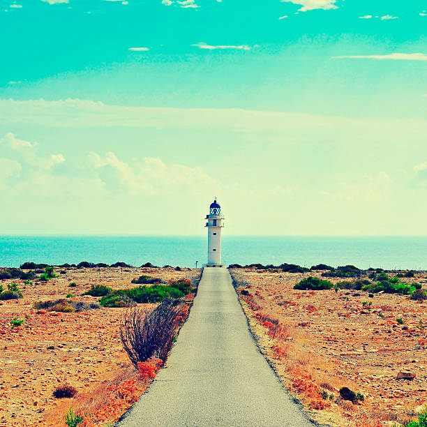 Straight road leading to a lighthouse in Formentera, Spain View of beacon Far de Barbaria in Formentera, Balearic Islands, Spain, with a retro effect beacon stock pictures, royalty-free photos & images