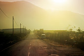 Retro style perspective of straight road and road side , sunset in the mist and row of street light posts. La Palma, Canary islands, Spain.