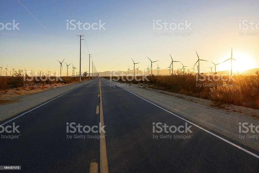 Straight road through the windfarm at sunset stock photo