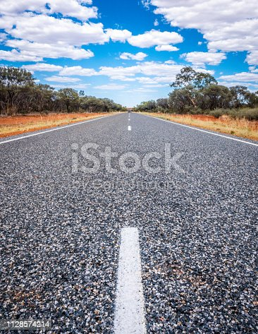 Straight road with white lines in middle of outback red center NT Australia