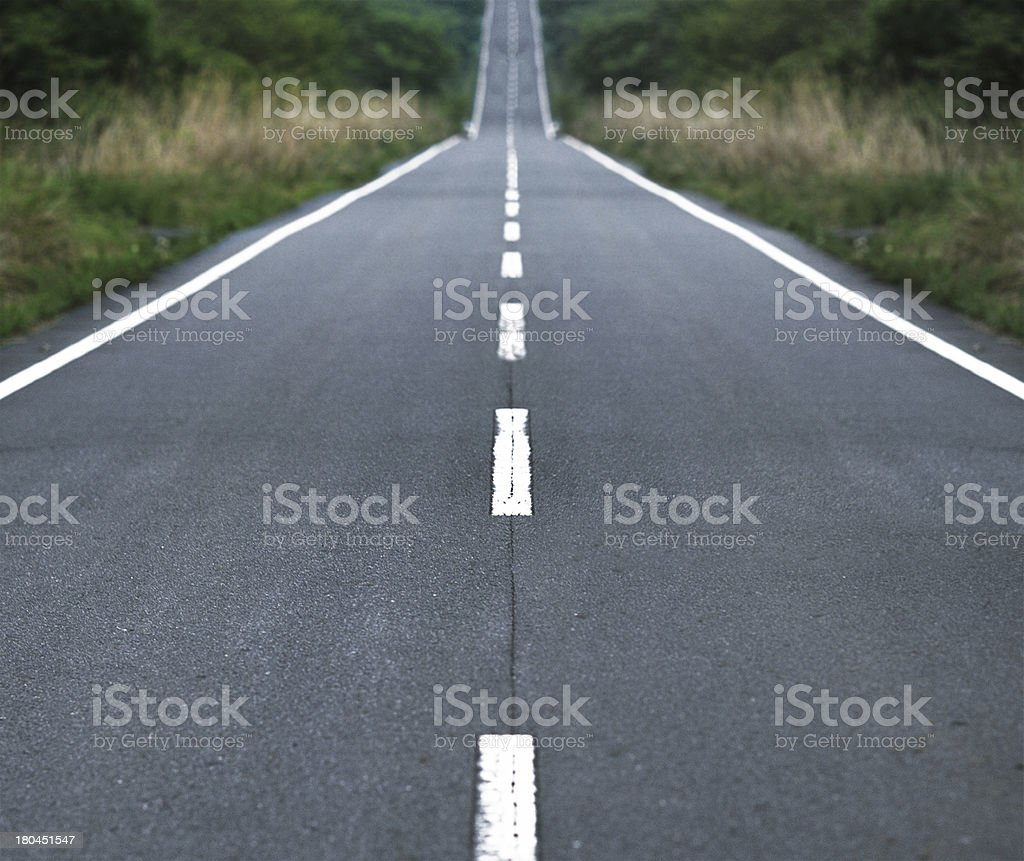 Straight tar road leading into the light stock photo