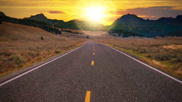 straight two lane highway with no traffic leads through a valley landscape toward a golden sunrise over the horizon ahead. conceptual for freedom, enjoying the journey, and a fresh new day. - dotted line stock photos and pictures