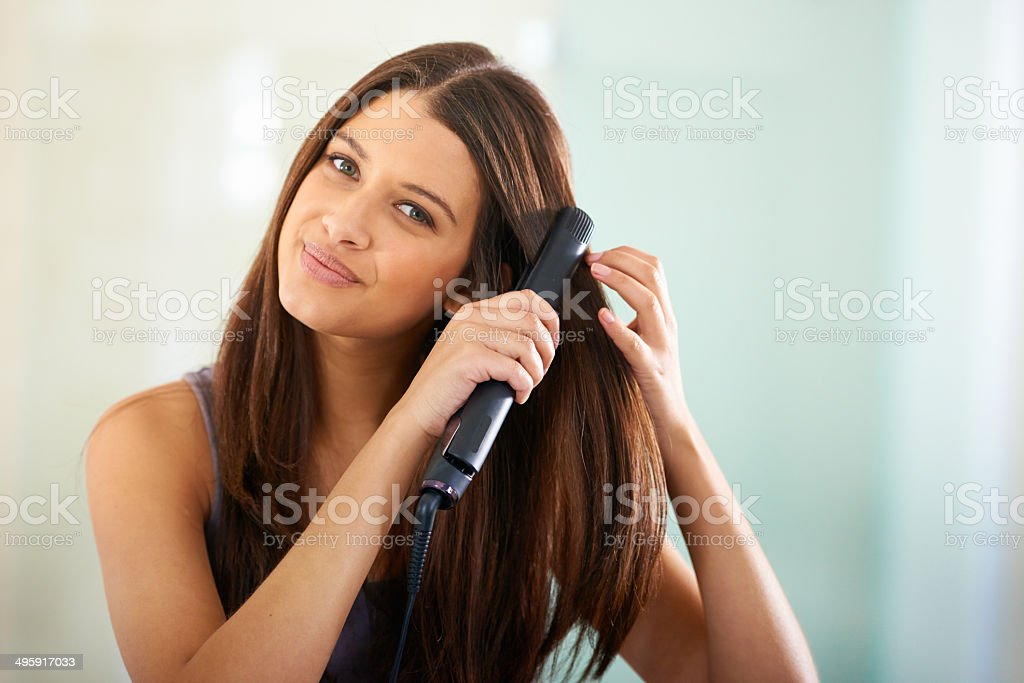 Straightening her hair for that sexy look stock photo