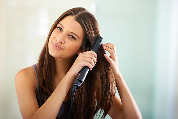 Straightening her hair for that sexy look Portrait of an attractive woman straightening her hair with a flat ironhttp://195.154.178.81/DATA/i_collage/pi/shoots/783430.jpg straight hair stock pictures, royalty-free photos & images