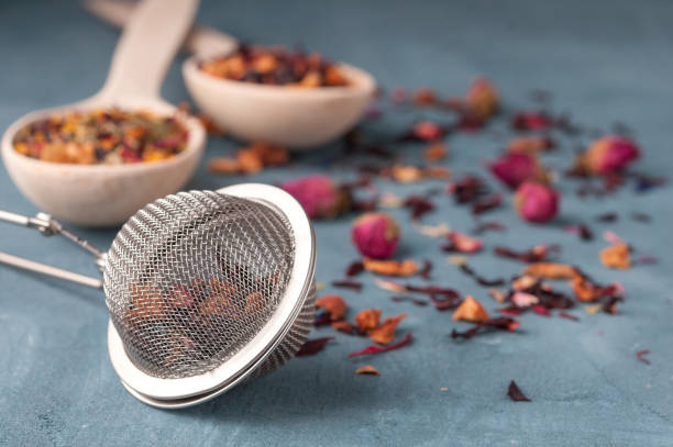 Strainer for brewing tea, different types of tea, spices and dried roses stock photo