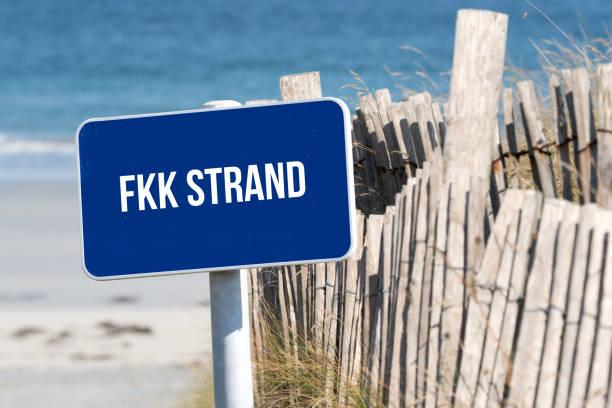 strand, meer und ein schild mit dem hinweis auf fkk strand - fkk strand stock-fotos und bilder