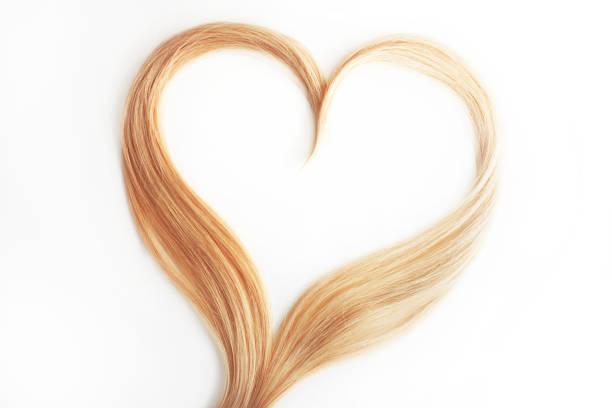 mechón de pelo rubio aislado en blanco. Rizos de pelo en forma de corazón - foto de stock
