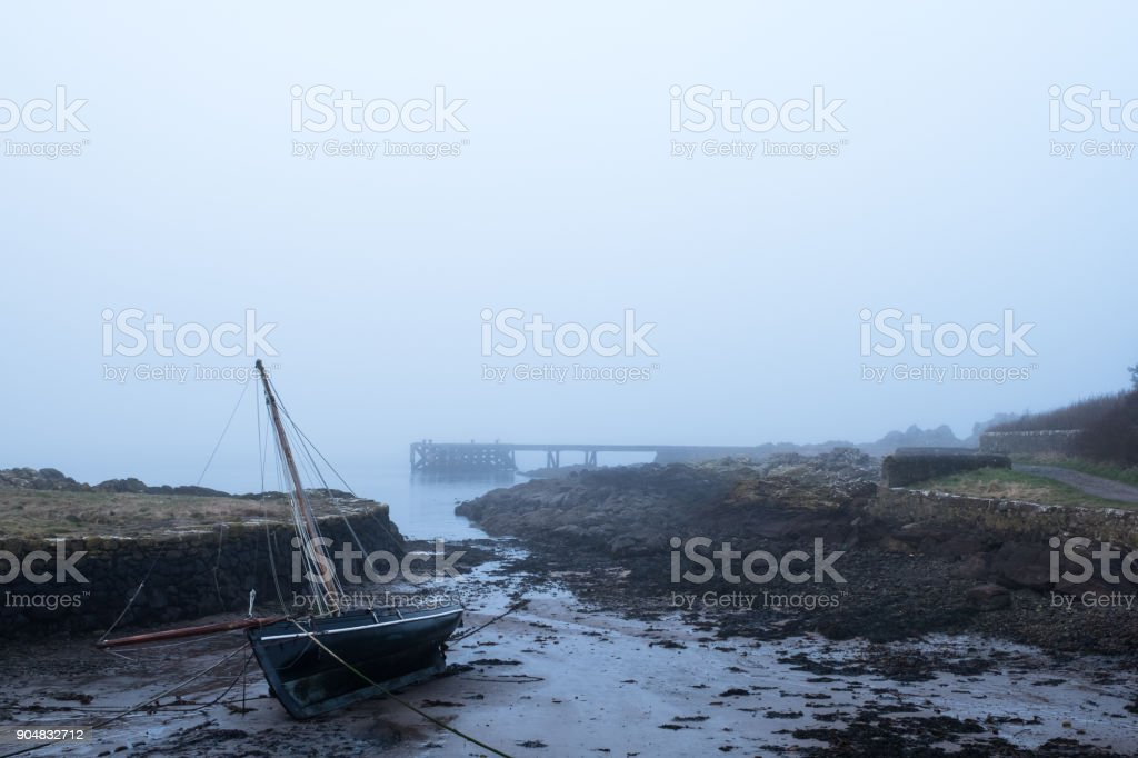 Stranded Boat on its side after the tide went out. stock photo