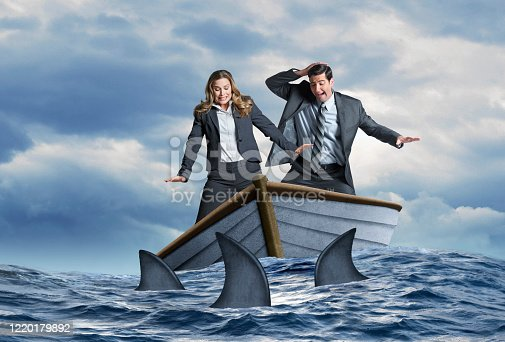 A fearful businessman and businesswoman look down in fear as they stand in a wooden dinghy that is surrounded by a school of sharks.