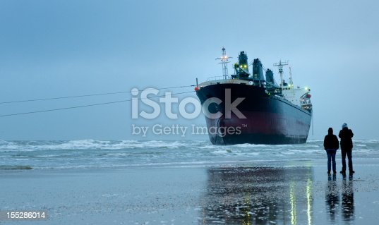 stranded empty illuminated container ship on the beach at dawn with two spectators on the beach