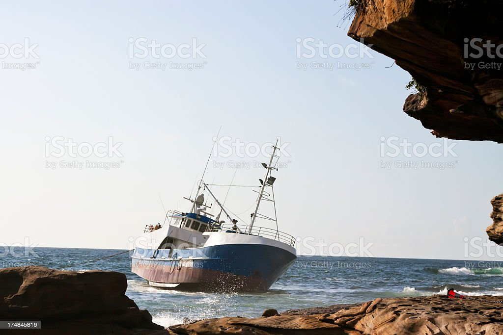Stranded fishing boat at the coastal rocks, copy space royalty-free stock photo