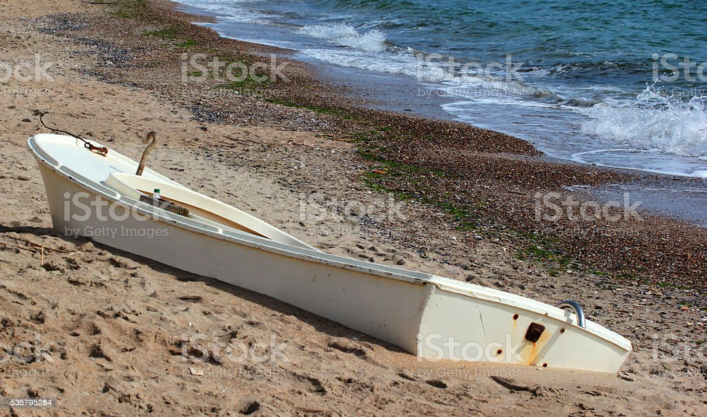 Stranded old motorboat on a deserted sandy beach stock photo