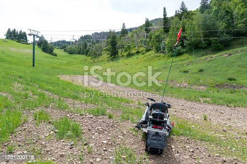 This is what looks like a forgotten snowmobile left next to a ski lift at a ski resort in the U.S. during the summer.  The mountain serviced by the ski lift is lush and green from all the snow that covered it during the winter and spring but the retreating snow has left the snowmobile high and dry.