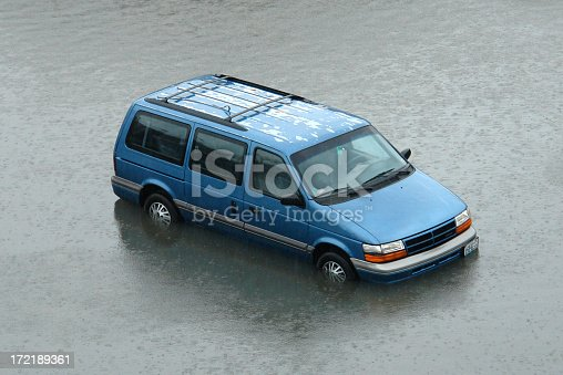 An abandoned van caught in the rising flood waters. No driver is visible through the windshield. The paint finish is peeling off the roof in some parts, but the vehicle is otherwise in good condition. The entire surroundings are consumed by the flood waters as a driving rain pelts the surface.