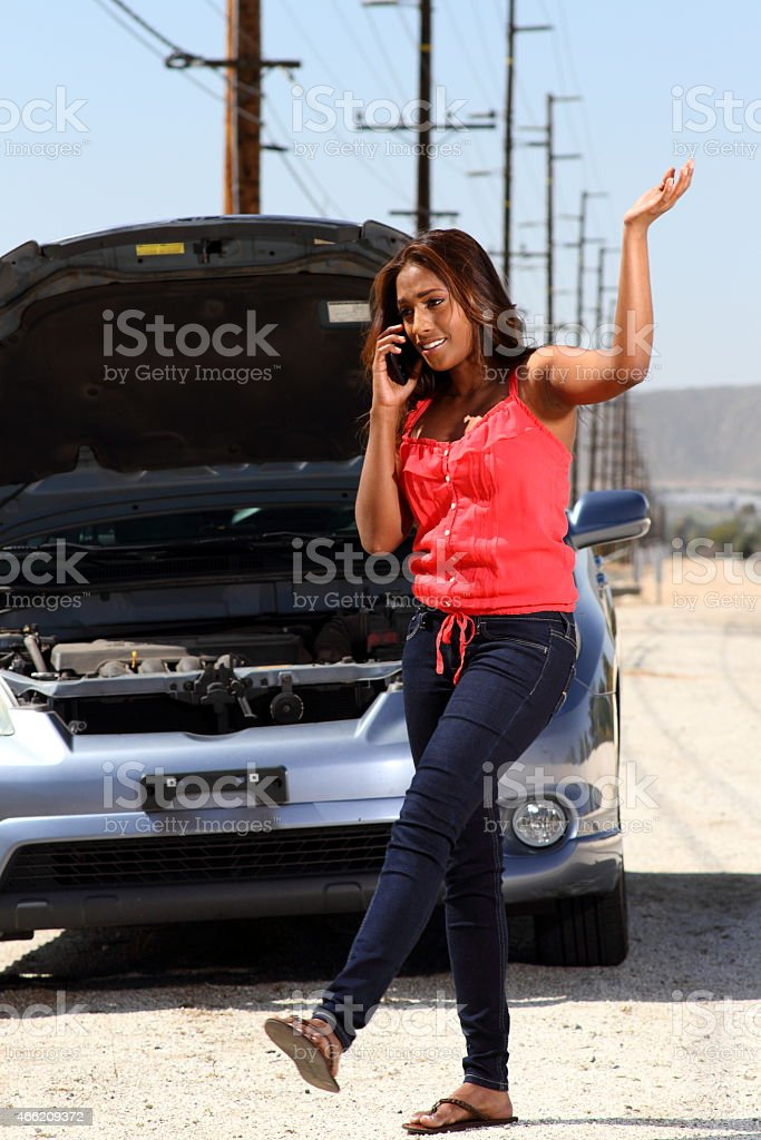 Stranded Young African American Motorist Mad on Phone stock photo