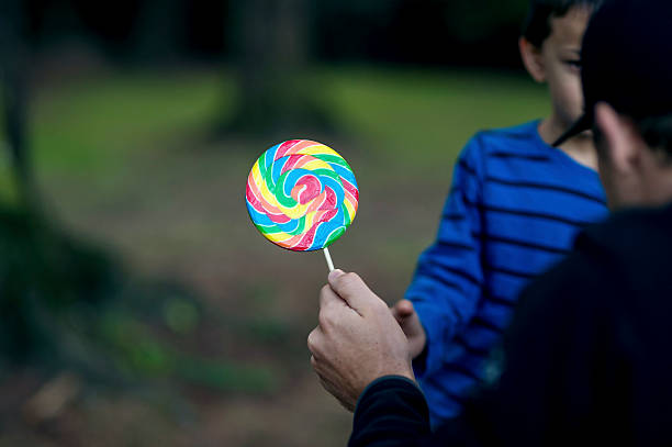 Strange adult male offering a young boy a lollipop Strange adult male offering a young boy a lollipop as he tries to lure him from the park stranger stock pictures, royalty-free photos & images