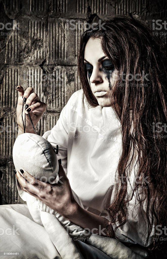 Estranho crazy garota com boneca moppet e needle em mãos - foto de acervo