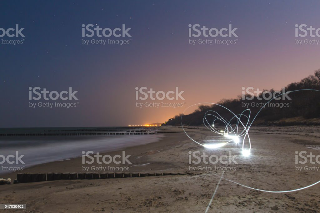 Strange futuristic light trails on beach stock photo