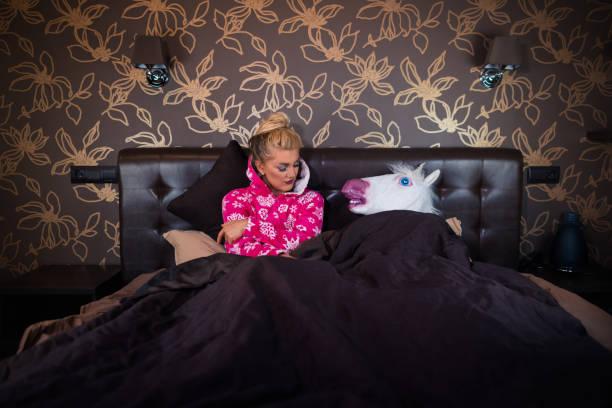 strange man in unicorn mask sleeping in bed near serious young woman - unicorn bed imagens e fotografias de stock