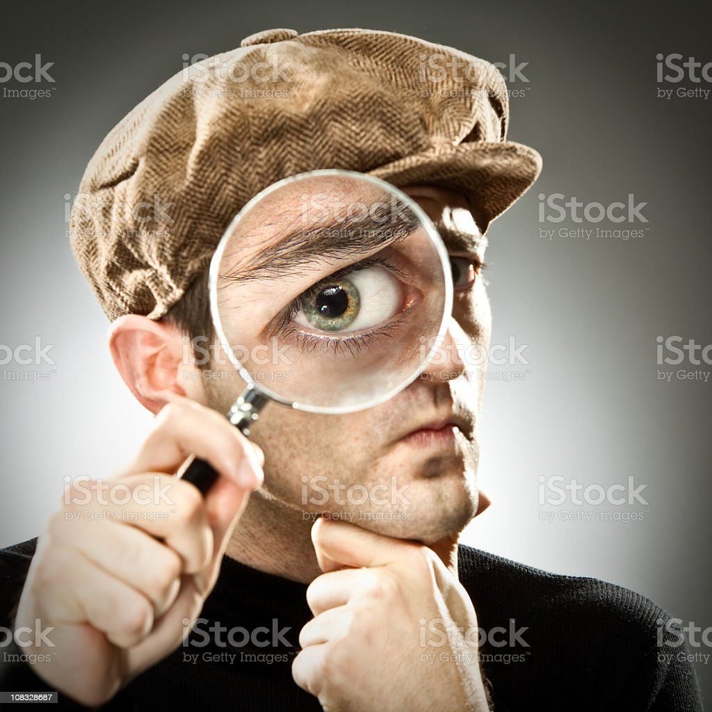 Strange man looking with magnifier glass on gray stock photo