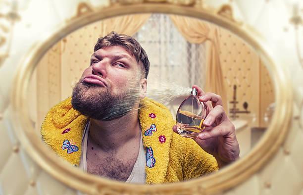 seltsamen mann parfüms selbst blick in den spiegel - ausgefallene mode für mollige stock-fotos und bilder
