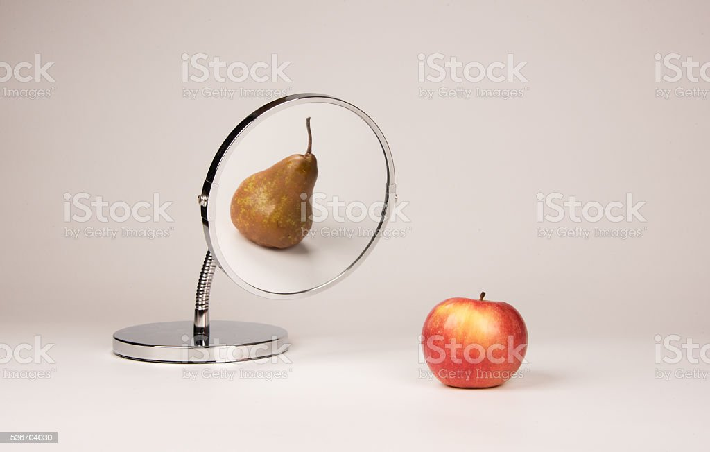 Strange mirror reflecting apple and pear stock photo