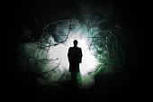 不気味な男と夜、神秘的な風景シュールなライトで暗い不気味な森で奇妙なシルエット。トーン