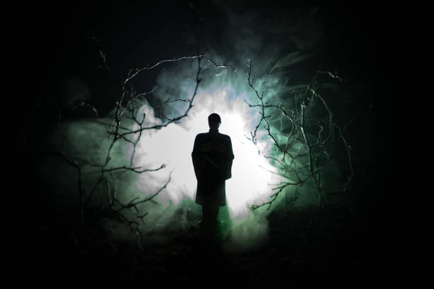 strange silhouette in a dark spooky forest at night, mystical landscape surreal lights with creepy man. toned - horror stock pictures, royalty-free photos & images