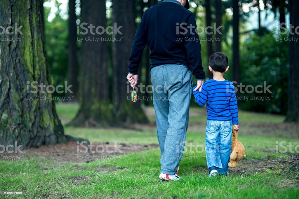 Stranger adult male kidnapping a young boy at the park stock photo