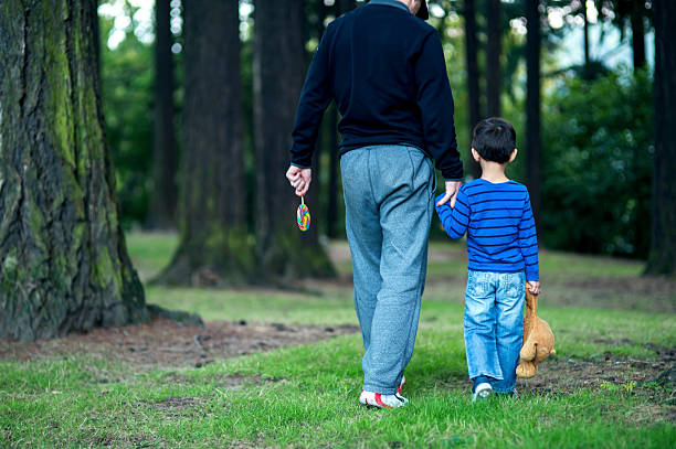 Stranger adult male kidnapping a young boy at the park Stranger adult male kidnapping a young boy at the park stranger stock pictures, royalty-free photos & images