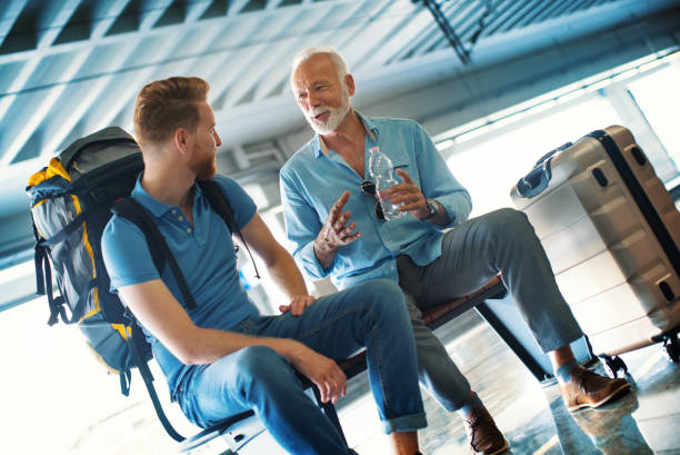 Strangers at a train station. Closeup of an early 60's man talking to a young guy while waiting for a train. He's talking about some nice and fun things from his past. stranger stock pictures, royalty-free photos & images