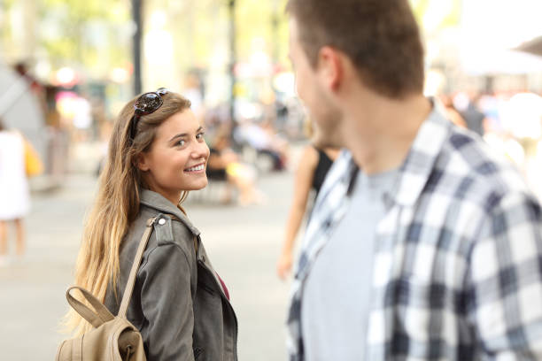 Strangers girl and guy flirting on the street Strangers girl and guy flirting looking each other on the street love at first sight stock pictures, royalty-free photos & images