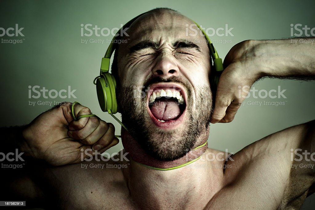 strangled by music: screaming man with green headphone royalty-free stock photo