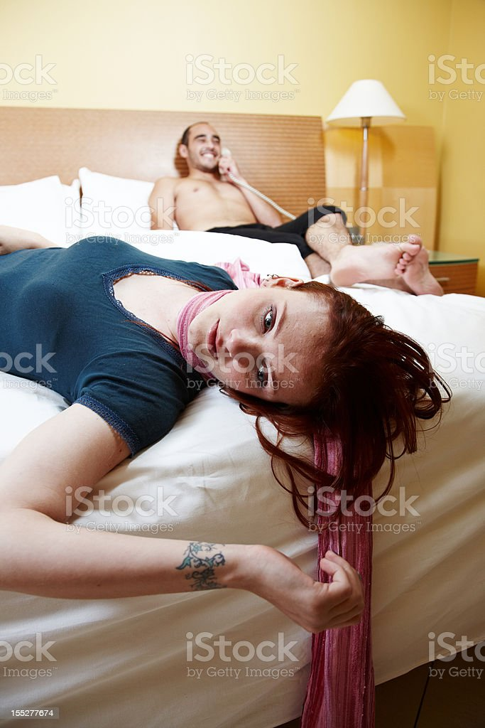 Strangled woman in bed man on phone stock photo