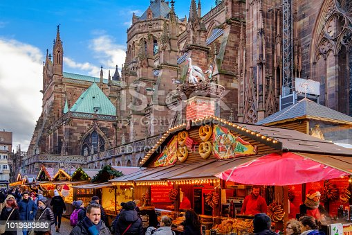 People at the Christmas market in Place de la Cathédrale of Strasbourg, considered the capital of the historical region of Alsace. The city is the official seat of the European Parliament.