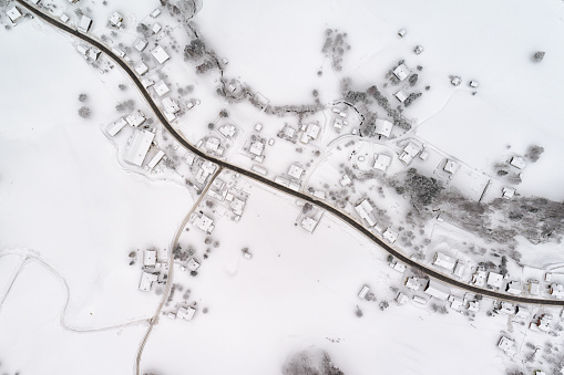 Aerial photograph of the small Austrian Village Strassen, Bad Aussee covered in Snow in the middle of the Austrian Alps.