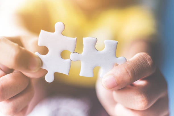 Strategic management and business solutions for success, Hand connecting jigsaw puzzle stock photo