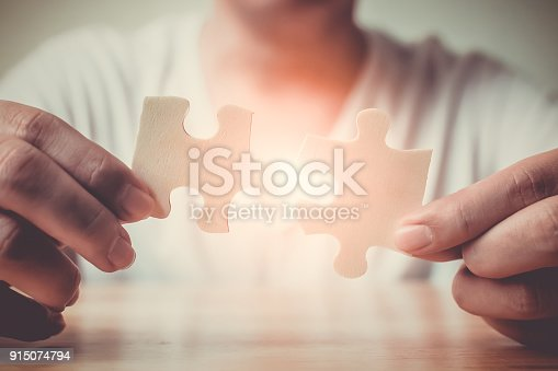 istock Strategic management and business solutions for success, Hand of male connecting jigsaw puzzle 915074794