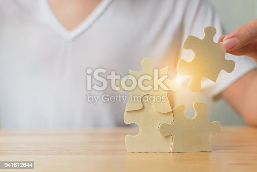 istock Strategic management and business solutions for success, Hand of male putting jigsaw puzzle connecting on woodden desk 941612644