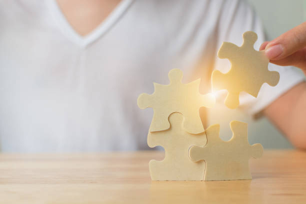 Strategic management and business solutions for success, Hand of male putting jigsaw puzzle connecting on woodden desk stock photo