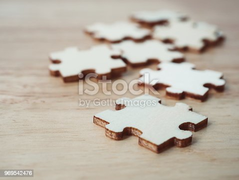 istock Strategic management and business solutions for success. Jigsaw puzzle connecting on wooden desk 969542476